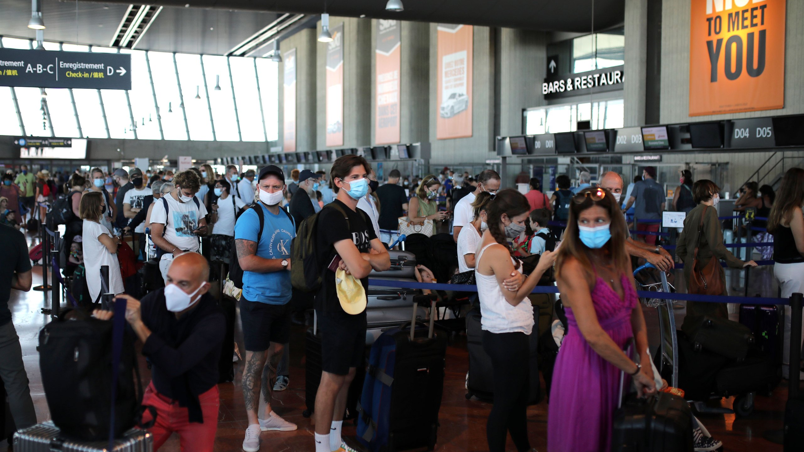 People queue in line to check-in for a British Airways flight to Heathrow airport, Friday Aug.14, 2020 at Nice airport, southern France. (AP Photo/Daniel Cole)