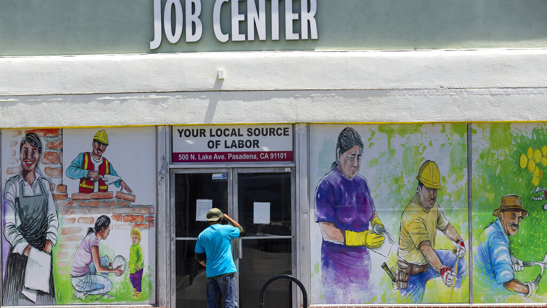 In this May 7, 2020, photo, a person looks inside the closed doors of the Pasadena Community Job Center in Pasadena during the coronavirus outbreak. (AP Photo/Damian Dovarganes, File)