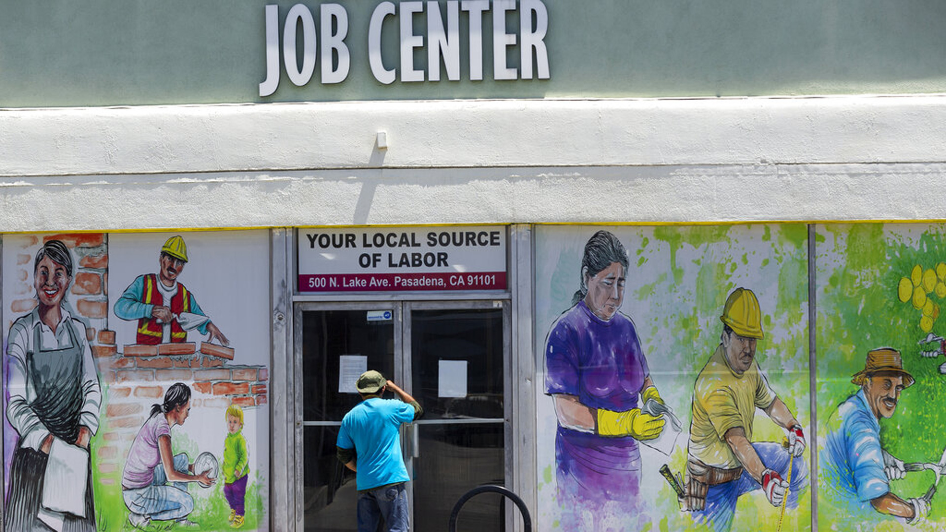 FILE - In this May 7, 2020, file photo, a person looks inside the closed doors of the Pasadena Community Job Center in Pasadena, Calif., during the coronavirus outbreak. (AP Photo/Damian Dovarganes, File)
