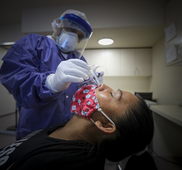 Family nurse practitioner Willie Rios collects a specimen for a coronavirus test from Araceli Merlos at St. John's Well Child and Family Center on July 29, 2020 in Los Angeles.(Irfan Khan / Los Angeles Times)