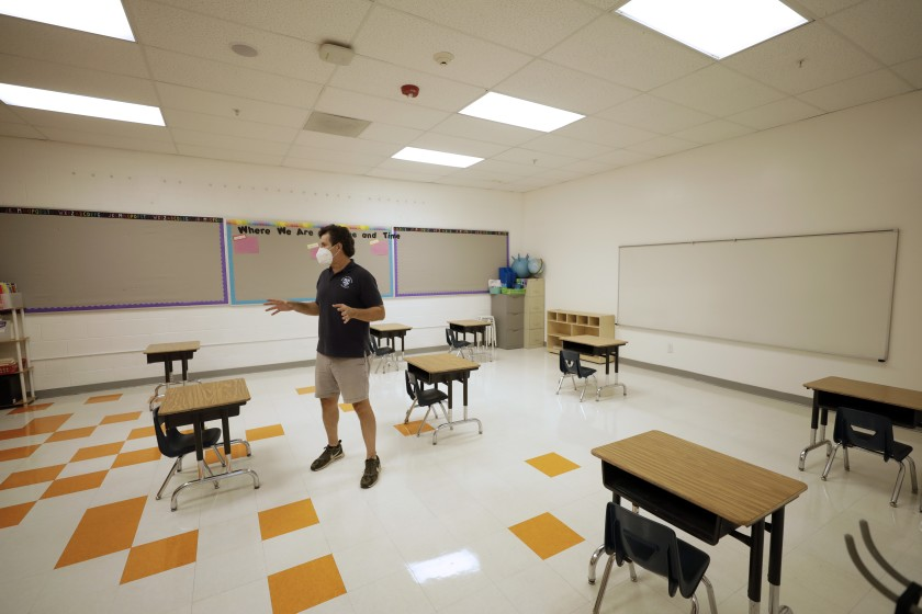 Xavier Reyes, cofounder of Alta Public Schools, shows what a classroom would look like at Academia Moderna, a charter school, when the Huntington Park campus is allowed to reopen. (Myung J. Chun / Los Angeles Times)