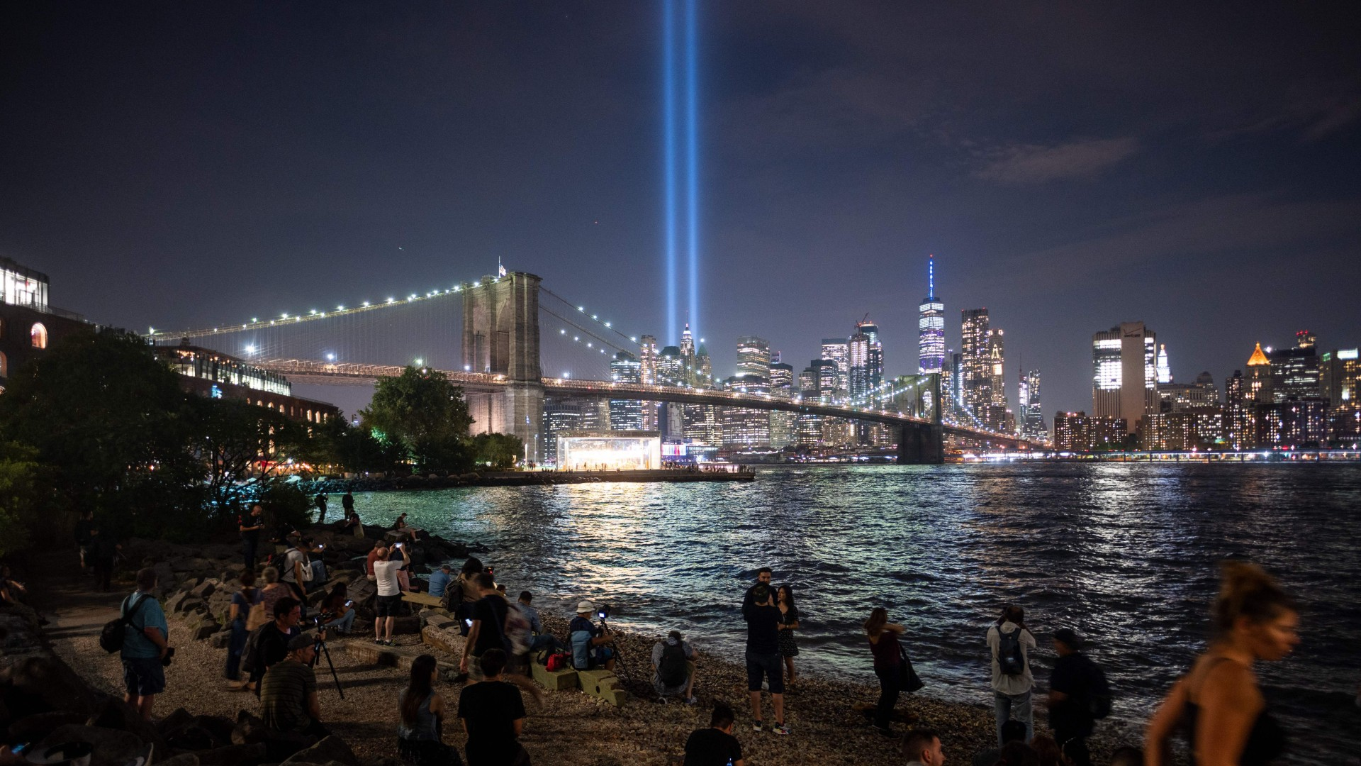 People on the shore watch The Tribute in Light shining into the sky over Manhattan's skyline on September 11, 2019 in New York. (JOHANNES EISELE/AFP via Getty Images)