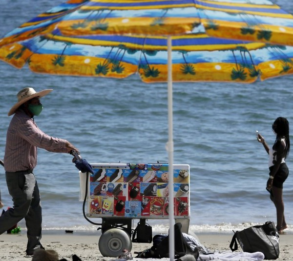An ice cream vendors pushes a cart along the sand at Junipero Beach in Long Beach on a warm afternoon in 2020. (Luis Sinco / Los Angeles Times)