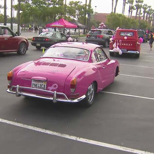 A pink car passes by in Tustin during a parade to raise breast cancer awareness. (KTLA)