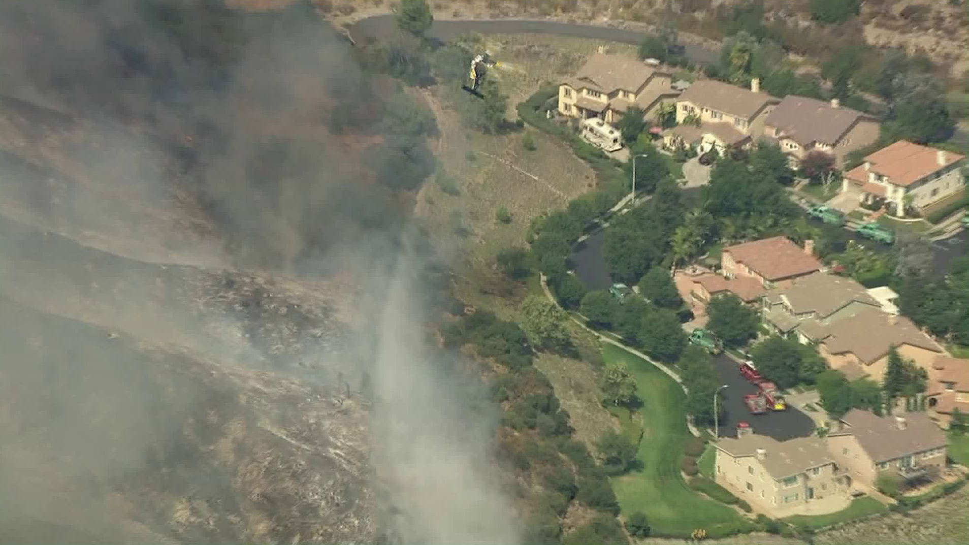 A helicopter drops water on an area of the Ranch Fire smoldering near homes in Azusa on Aug. 13, 2020. (KTLA)