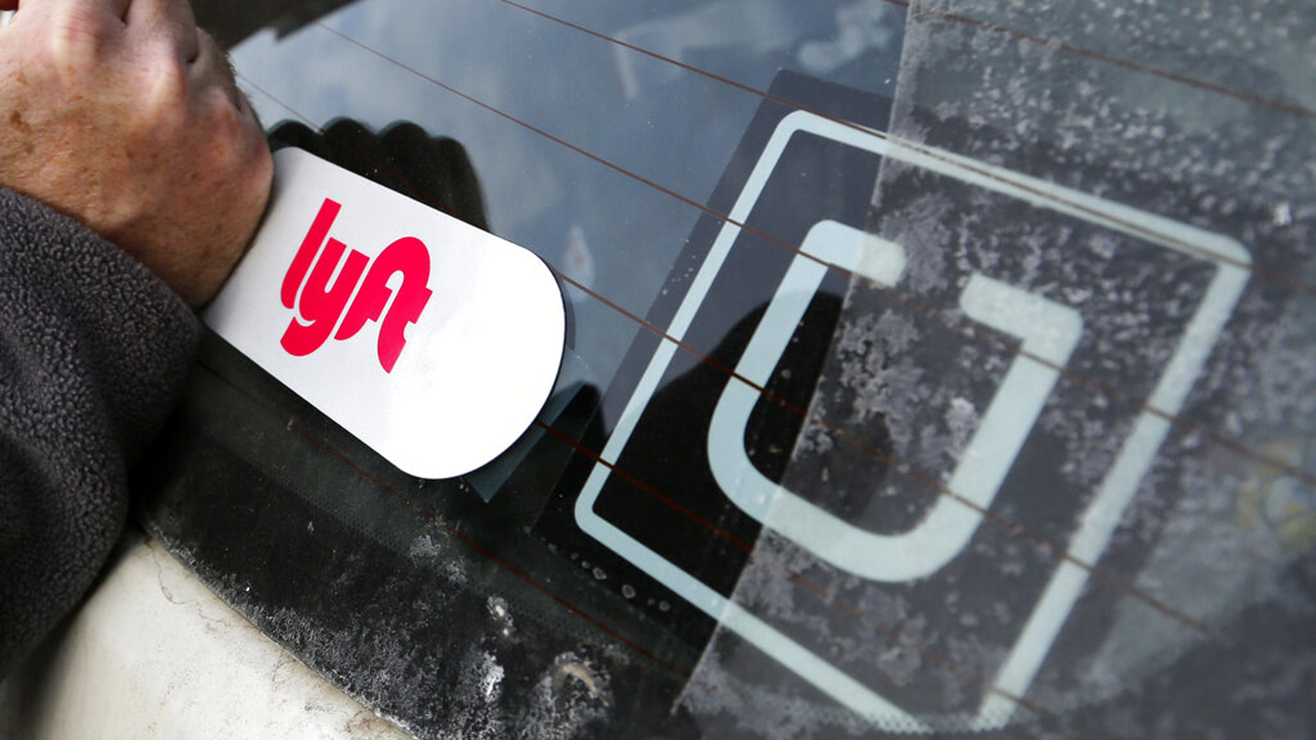 In this Jan. 31, 2018, file photo, a Lyft logo is installed on a Lyft driver's car next to an Uber sticker in Pittsburgh. (AP Photo/Gene J. Puskar, File)