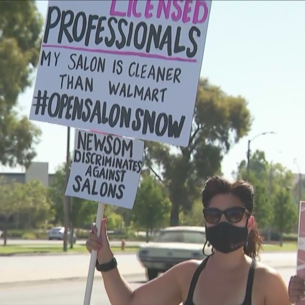 People hold signs during a Santa Clarita protest on Aug. 1, 2020 demanding the reopening of salons in California. (KTLA)