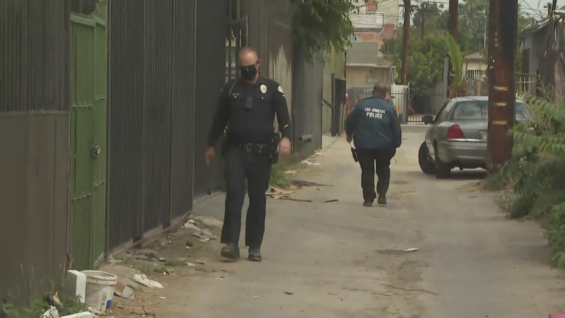 Investigators walk through an alleyway in the Florence neighborhood of South Los Angeles on Aug. 13, 2020, after a man was fatally struck in a hit-and-run crash there the night before. (KTLA)
