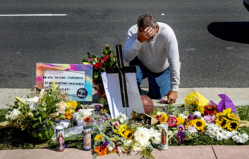 Danny Blain is overcome with emotion on Sept. 25, 2020, as he kneels at a memorial for Kurt Andras Reinhold, 42, a homeless Black man who was shot by Orange County deputies after they stopped him for jaywalking. (Gina Ferazzi/Los Angeles Times)