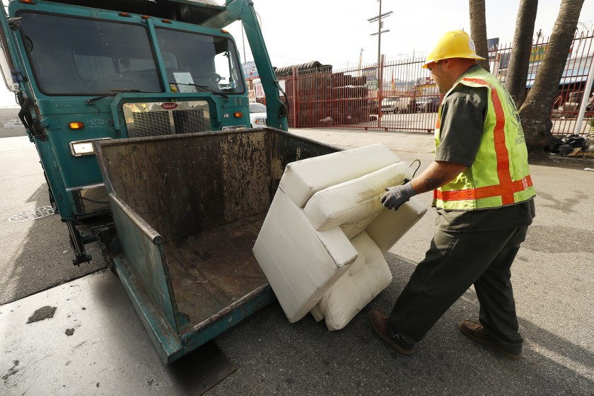 A Los Angeles sanitation worker removes a chair from the area of 41st Place and Alameda Street in an undated photo. (Al Seib / Los Angeles Times)