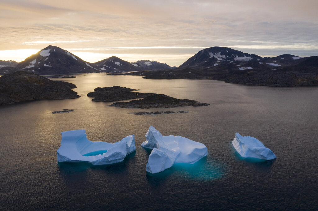 In this Aug. 16, 2019 file photo, icebergs float away as the sun rises near Kulusuk, Greenland. According to a study released on Thursday, Aug. 20, 2020, Greenland lost a record amount of ice during an extra warm 2019, with the melt massive enough to cover California in more than four feet (1.25 meters) of water. (AP Photo/Felipe Dana, File)