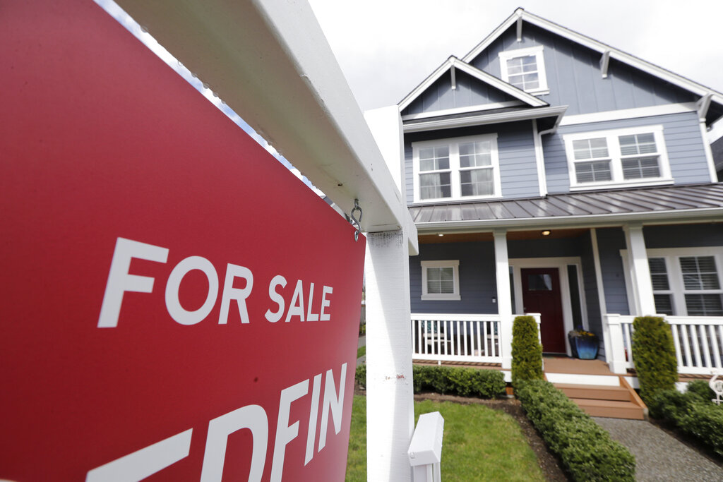 "In this April 1, 2020 photo, a ""For Sale"" sign stands in front of a home that is in the process of being sold in Monroe, Wash., outside of Seattle. (AP Photo/Elaine Thompson, File)"
