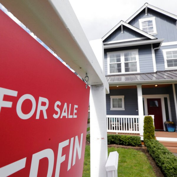 """In this April 1, 2020 photo, a """"For Sale"""" sign stands in front of a home that is in the process of being sold in Monroe, Wash., outside of Seattle. (AP Photo/Elaine Thompson, File)"""