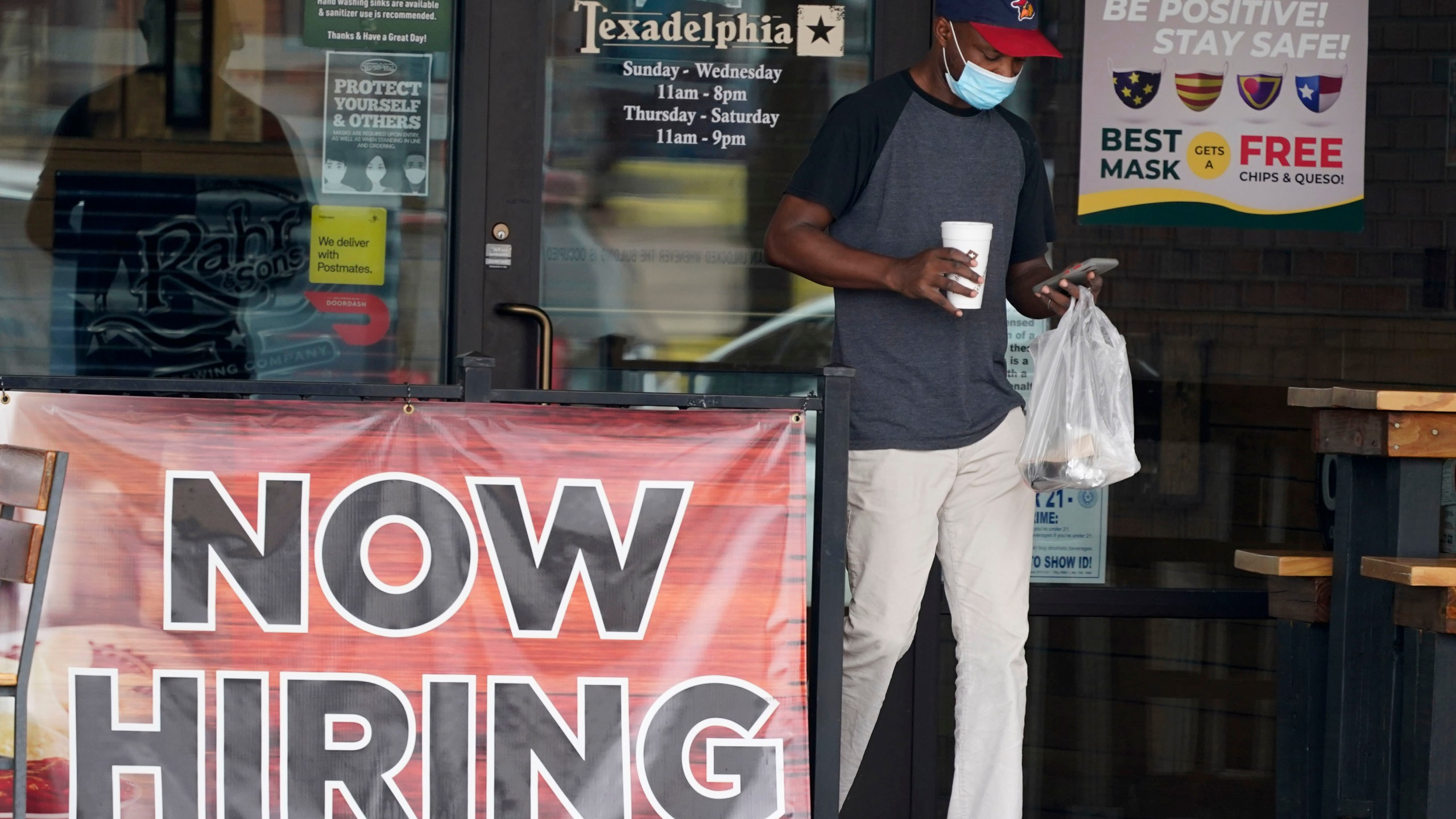 In this Sept. 2, 2020, file photo, a customer walks past a now hiring sign at an eatery in Richardson, Texas. The Labor Department reported unemployment numbers Thursday, Sept. 3. (AP Photo/LM Otero, File)