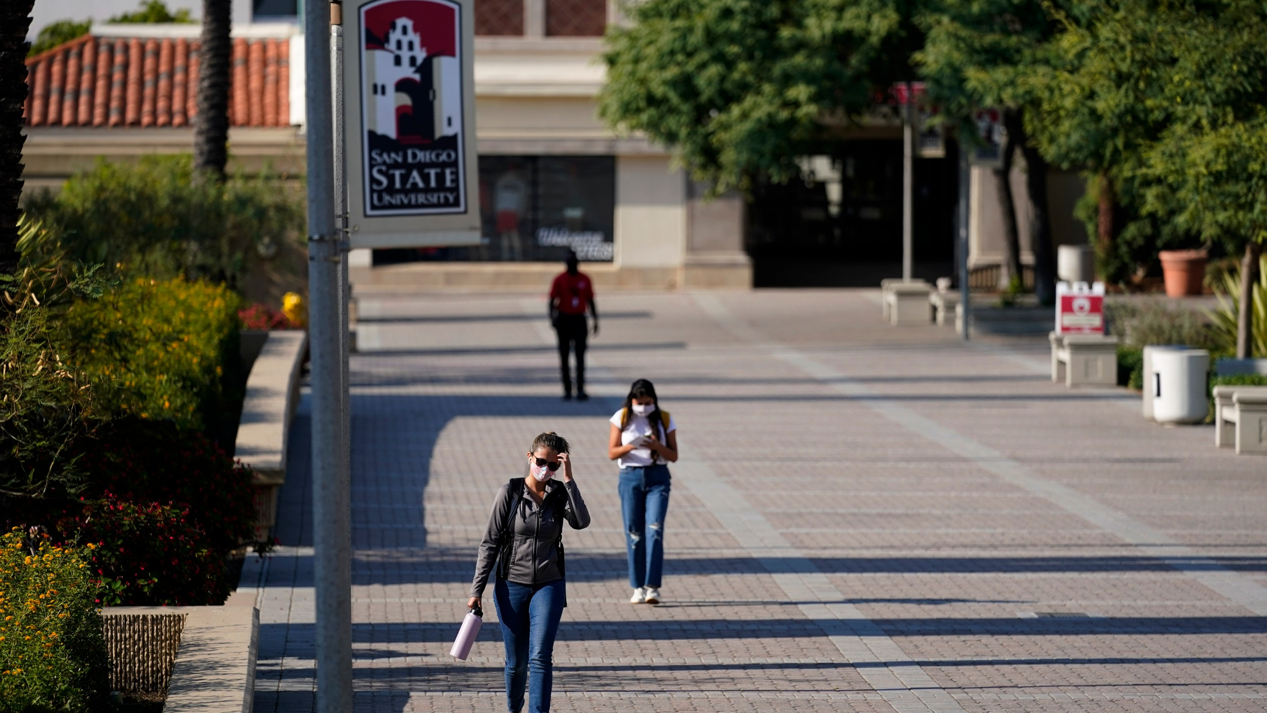 People walk on campus at San Diego State University on Sept. 2, 2020. The university halted in-person classes for a month after dozens of students were infected with the coronavirus. (Gregory Bull/Associated Press)