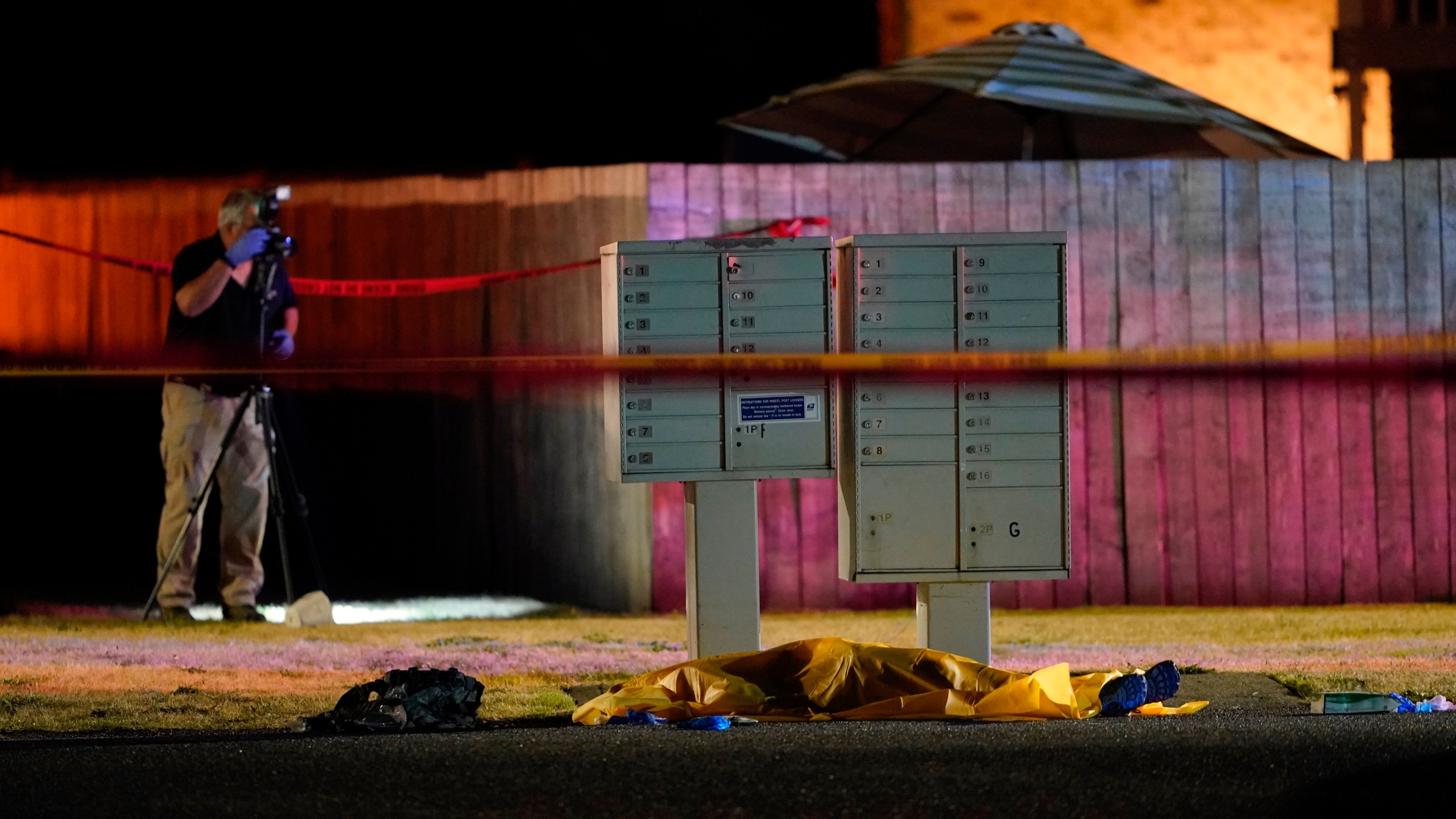 Officials work at a scene late on Sept. 3, 2020, where a man suspected of fatally shooting a supporter of a right-wing group in Portland, Oregon, the week before was killed as investigators moved in to arrest him in Lacey, Washington. (Ted Warren / Associated Press)