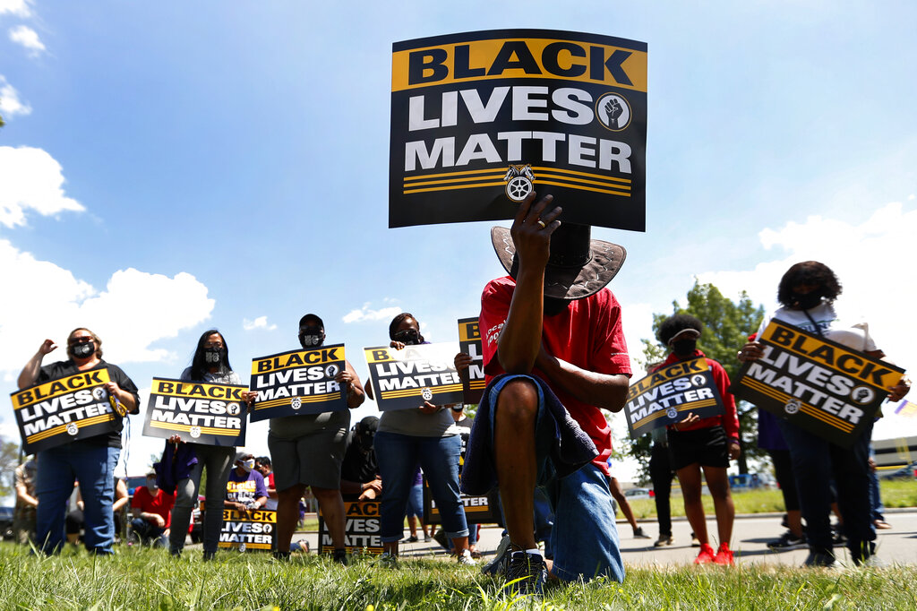 In this July 20, 2020, file photo, Eddie Perkins takes a knee during a protest rally outside Hartford Nursing & Rehabilitation Center in Detroit. (AP Photo/Paul Sancya, File)