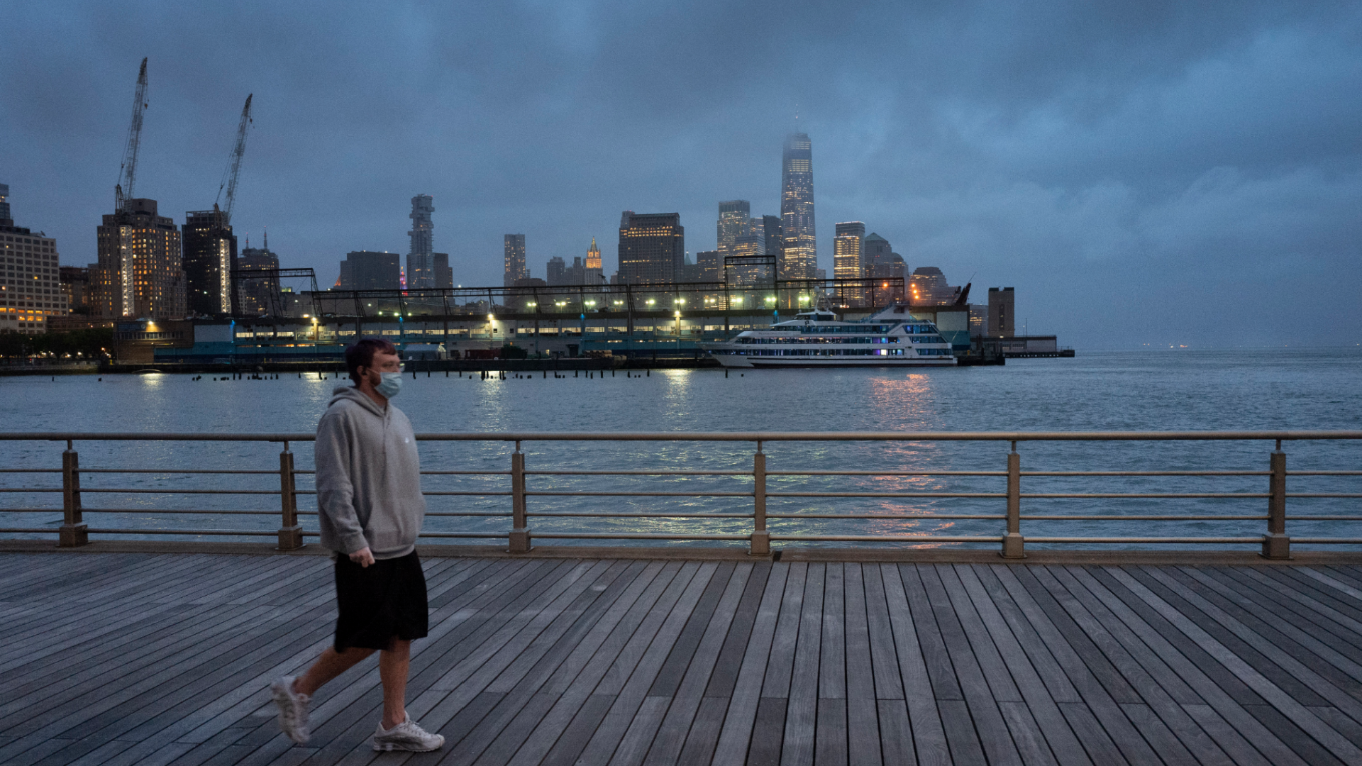 In this April 30, 2020, file photo, a man wears a face mask as he walks on Pier 45 in Hudson River Park in New York. (AP Photo/Mark Lennihan, File)