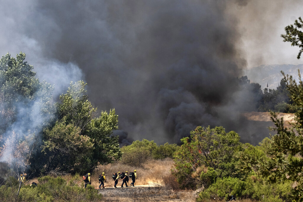 Los Angeles Fire Department firefighters hike into the Sepulveda Basin to fight a brush fire in the Sherman Oaks area of Los Angeles, Sunday, Sept. 6, 2020. (AP Photo/Richard Vogel)