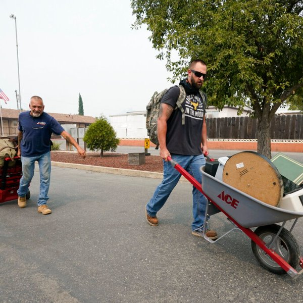 Two men take out their belongings on wheel barrows during a mandatory evacuation due to the Creek Fire Sept. 7, 2020, in Auberry, Calif. (AP Photo/Marcio Jose Sanchez)