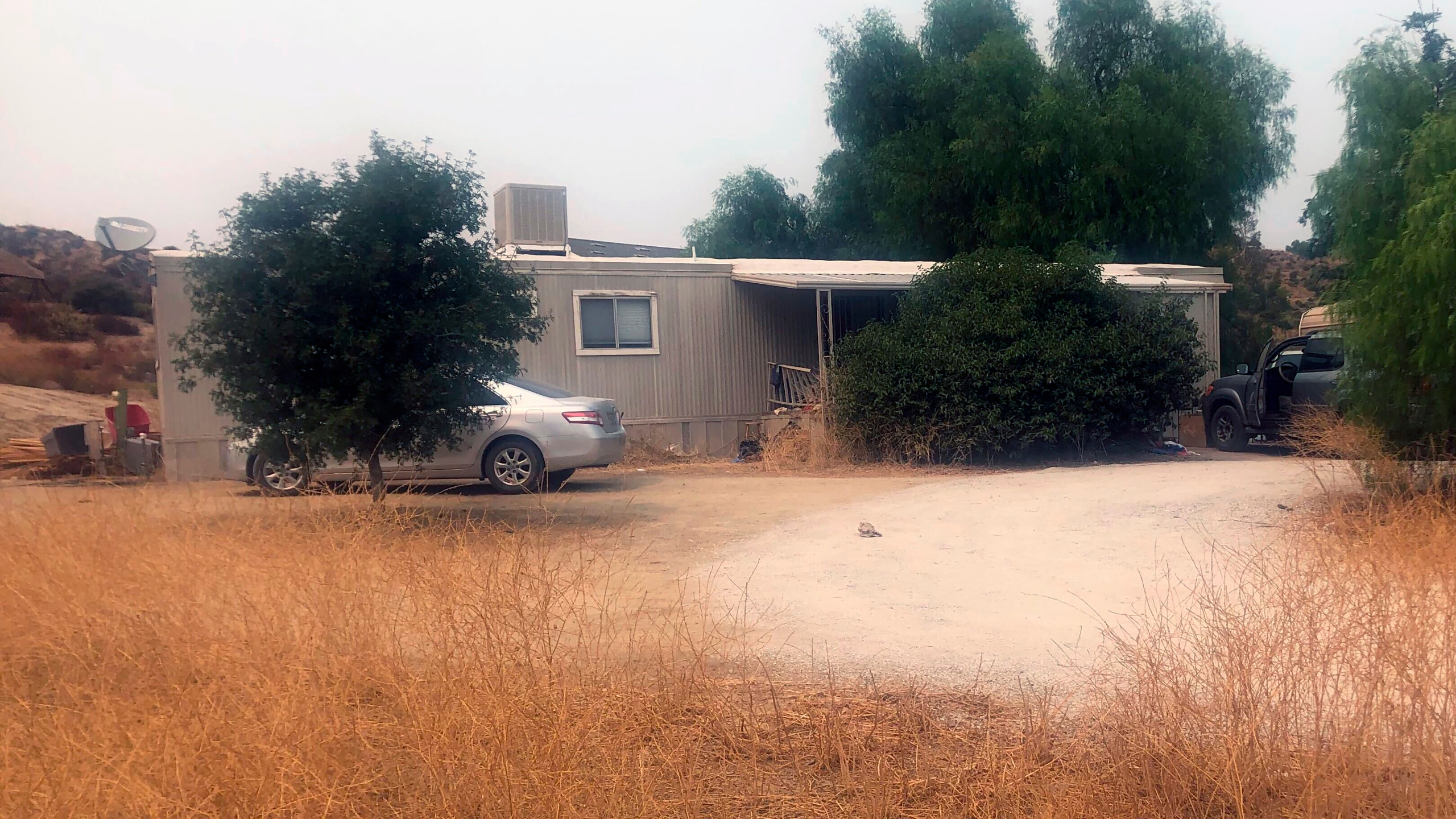 A car is left parked at a house where killings occurred in the rural town Aguanga, Calif., Tuesday, Sept. 8, 2020. Seven people were found fatally shot at an illegal marijuana growing operation in Aguanga. The crime scene was discovered before dawn Monday, Sept. 7, after deputies responded to a report of an assault with a deadly weapon at a home in the unincorporated community of Aguanga, north of San Diego, the Riverside County Sheriff's Department said in a statement. (AP Photo/Elliot Spagat)