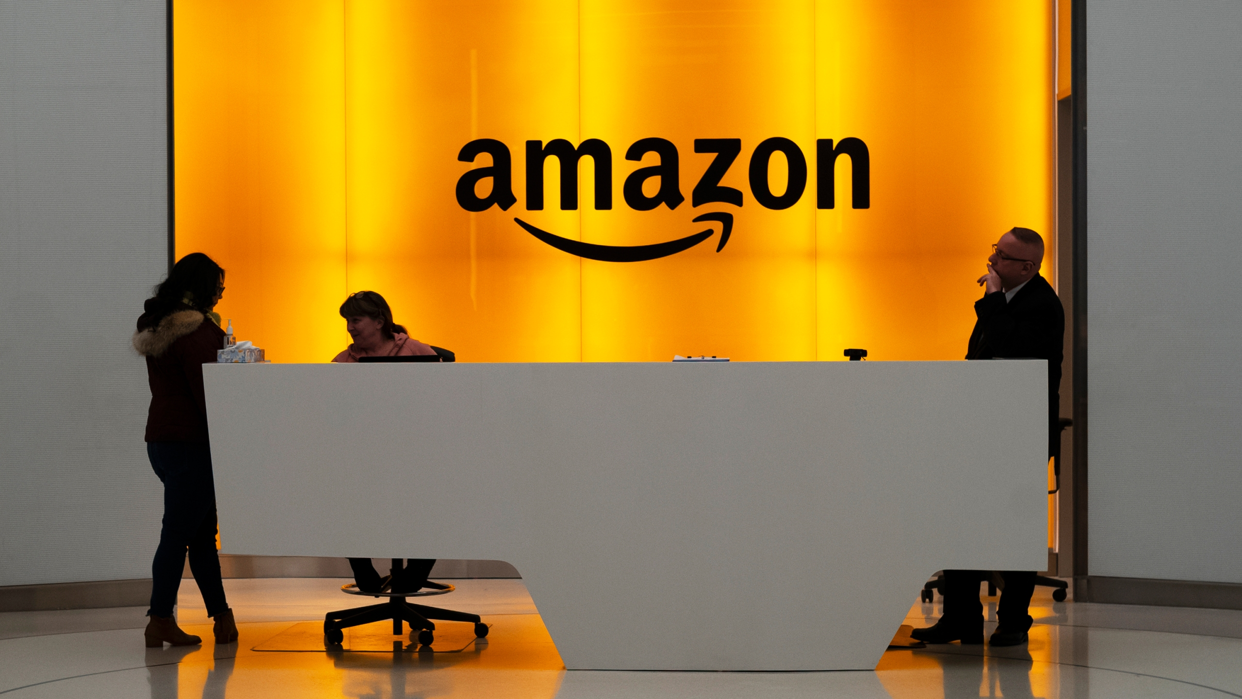 In this Feb. 14, 2019, photo, people stand in the lobby for Amazon offices in New York. (AP Photo/Mark Lennihan, File)