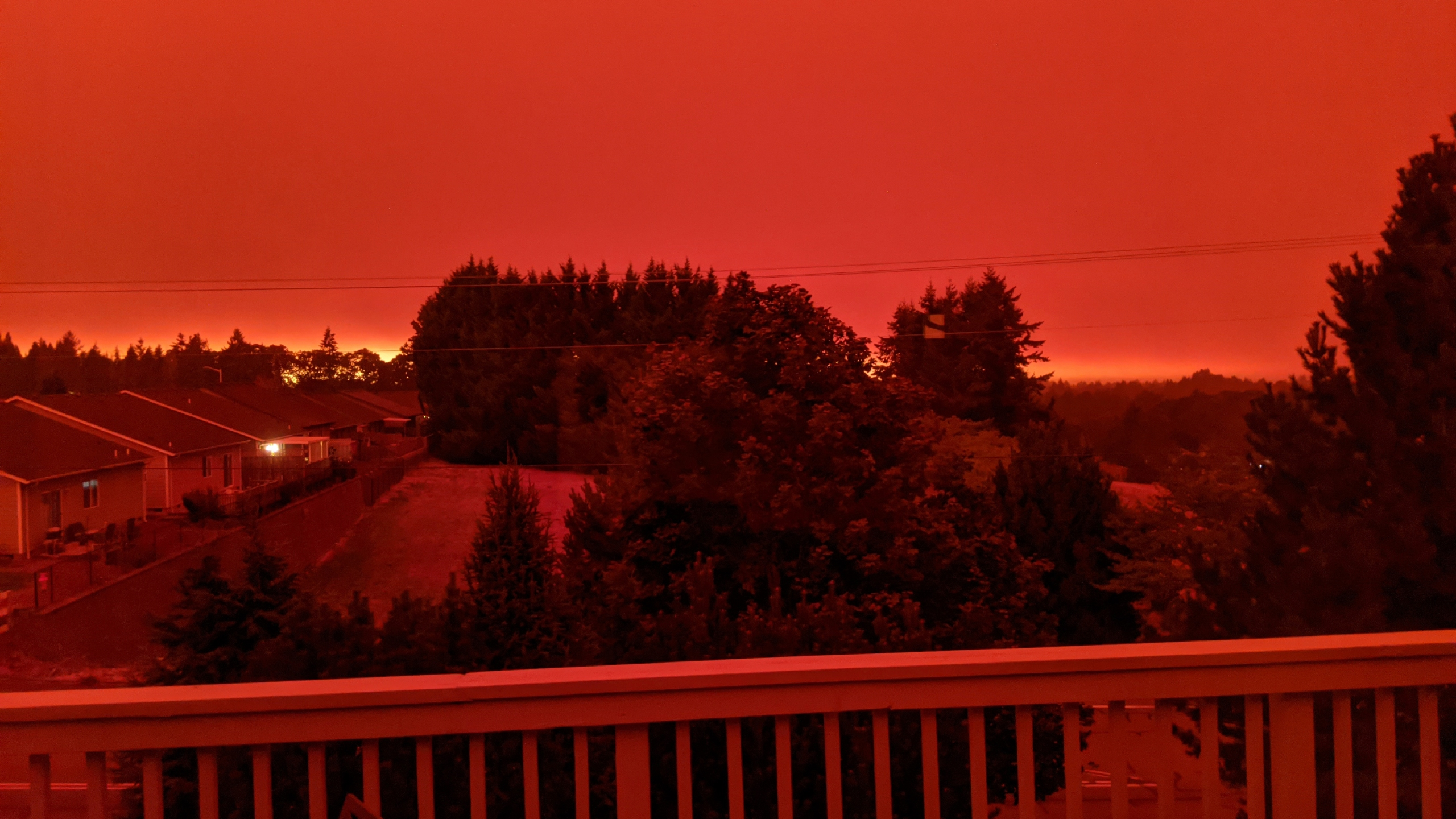 This photo taken from the home of Russ Casler in Salem, Ore., shows the smoke-darkened sky well before sunset at around 5 p.m., Tuesday, Sept. 8, 2020. Strong winds and high temperatures continued to fuel catastrophic fires in many parts of Oregon on Wednesday, forcing thousands of people to flee from their homes and making for poor air quality throughout the West. Huge wildfires also continued to grow in neighboring Washington state. (Russ Casler via AP)