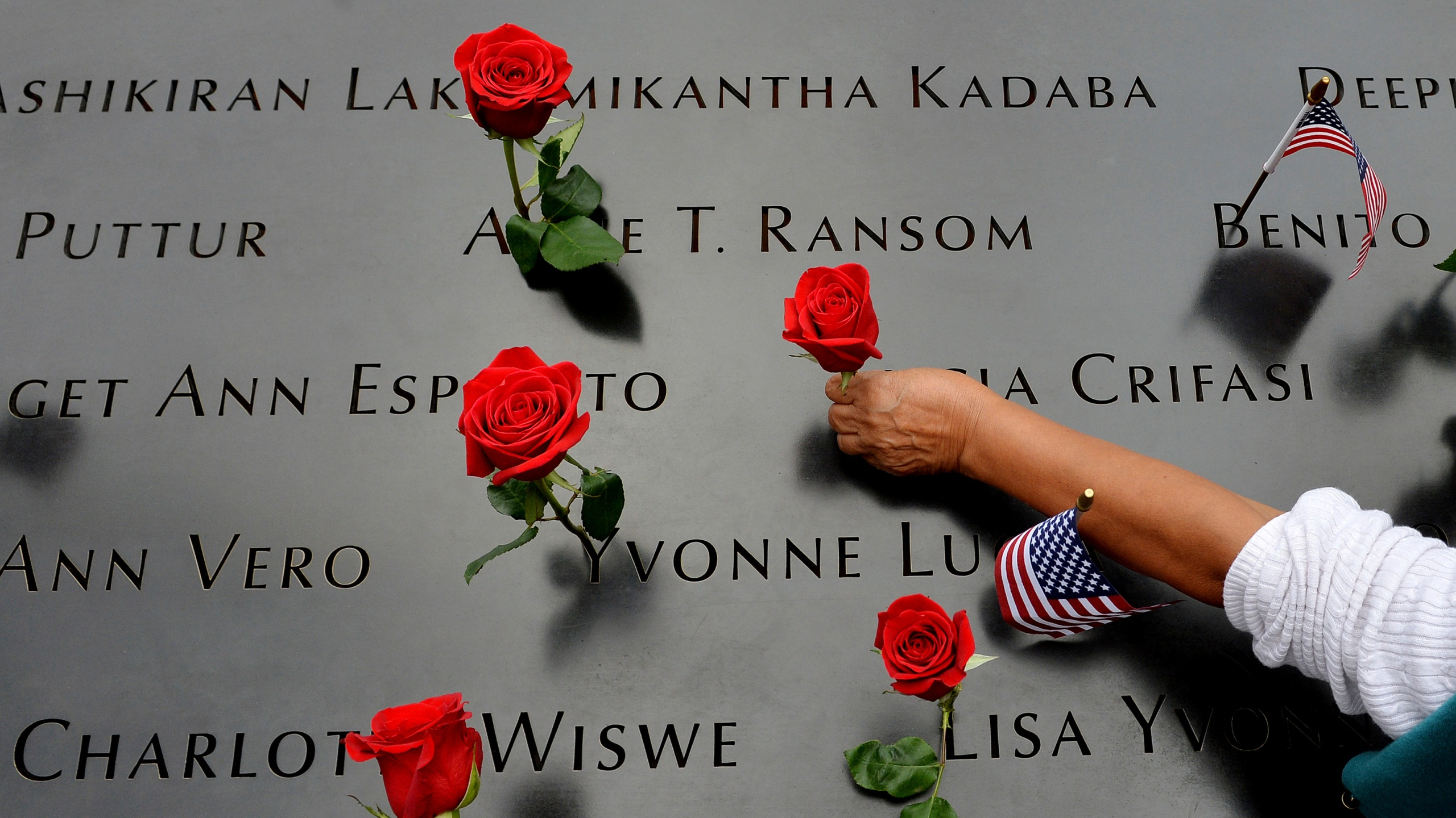 In this Sept. 11, 2014, photo, a woman places flowers in the inscribed names along the edge of the North Pool during memorial observances on the 13th anniversary of the Sept. 11, 2001, terror attacks on the World Trade Center in New York. (AP Photo/Justin Lane, Pool, File)