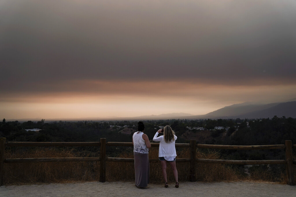 Two people watch smoke generated by the Bobcat Fire in San Dimas on Sept. 9, 2020. (AP Photo/Jae C. Hong)
