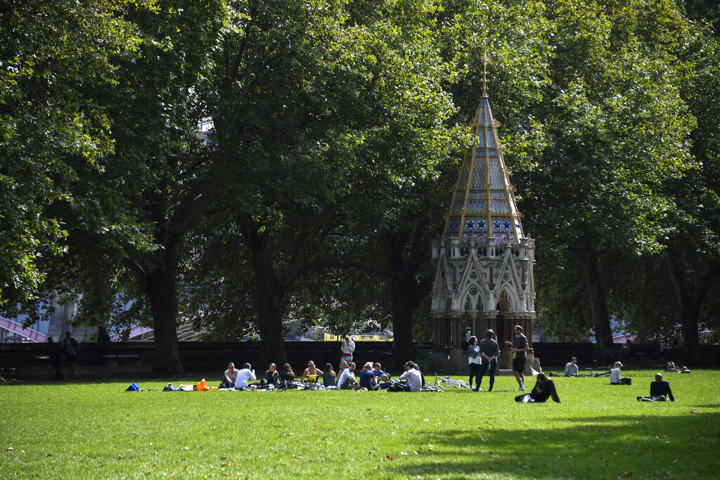 People sit on the grass at Victoria Gardens, in London, Thursday, Sept. 10, 2020. (AP Photo/Alberto Pezzali)