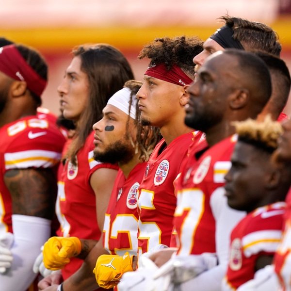 Kansas City Chiefs players, including quarterback Patrick Mahomes, No. 15, stand with teammates for a presentation on social justice before an NFL football game against the Houston Texans in Kansas City, Missouri, on Sept. 10, 2020. (Charlie Riedel / Associated Press)