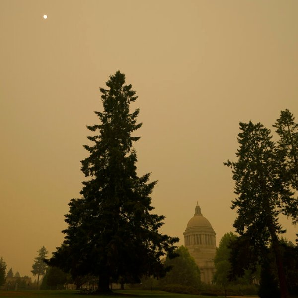 Smoke from wildfires in Oregon and California creates hazy skies as the sun is seen above the Washington state Capitol, Saturday afternoon, Sept. 12, 2020, in Olympia, Wash. (AP Photo/Ted S. Warren)