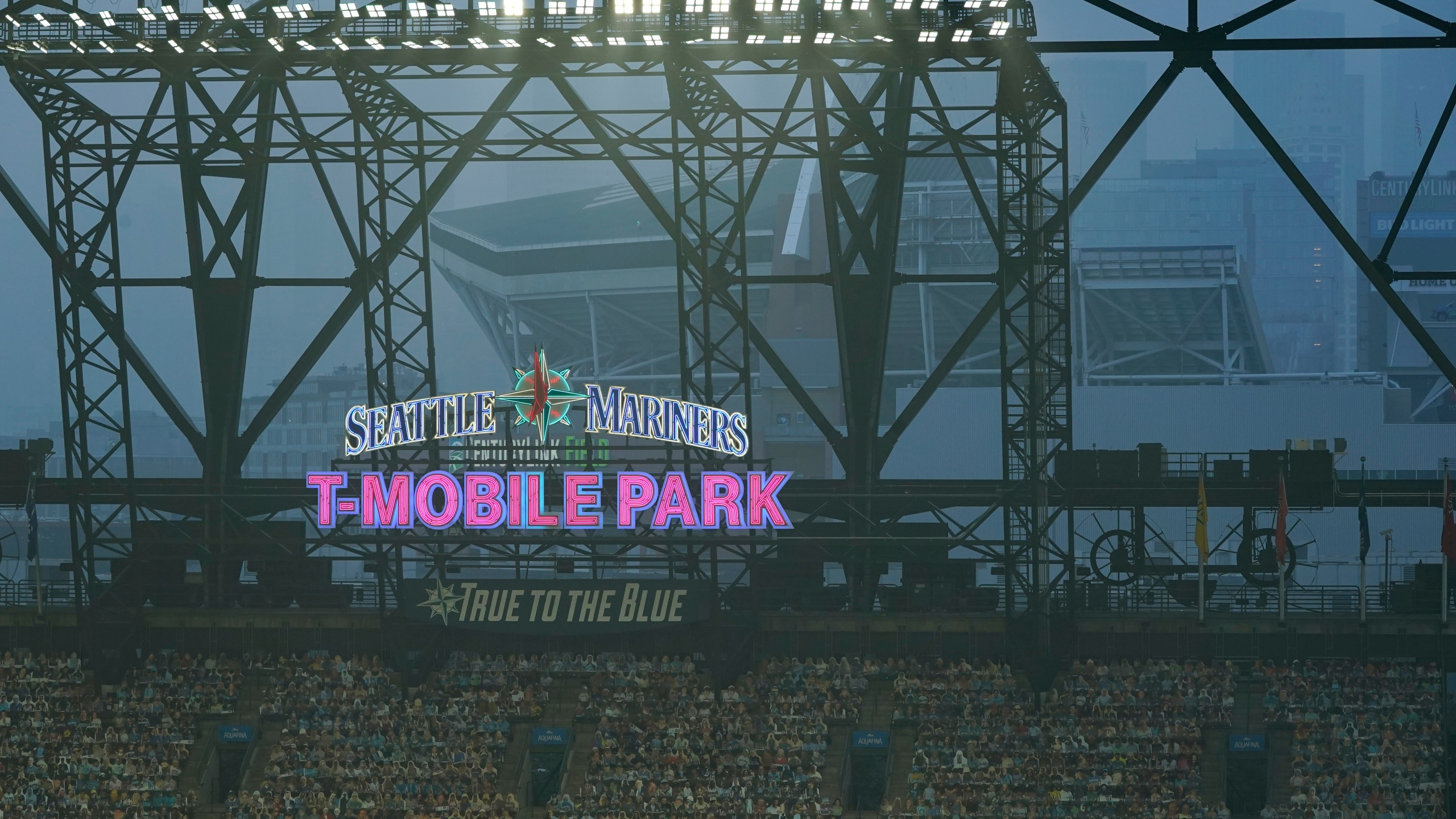 Smoke from wildfires fills the air at T-Mobile Park as photos of fans are displayed in the left field bleachers and CenturyLink Field is visible behind the ballpark sign during the second baseball game of a doubleheader between the Seattle Mariners and the Oakland Athletics, Sept. 14, 2020, in Seattle. (Ted S. Warren / Associated Press)