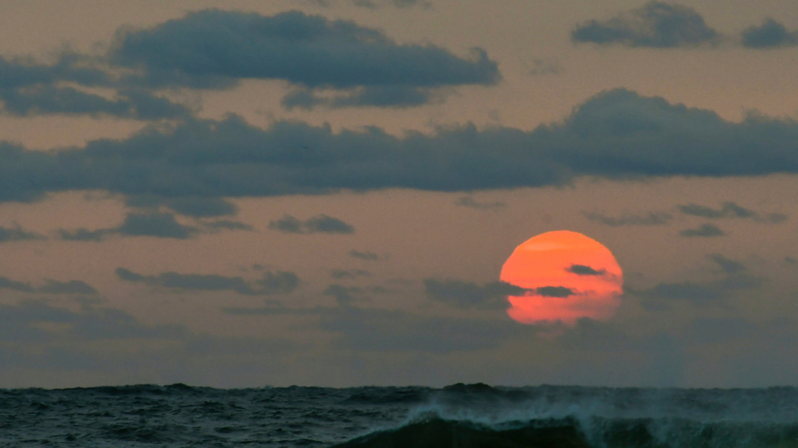This photo taken at sunrise from Surf City on Long Beach Island in New Jersey shows the sun shrouded in smoke and brown haze Tuesday, Sept. 15, 2020. (Elizabeth Laird via AP)