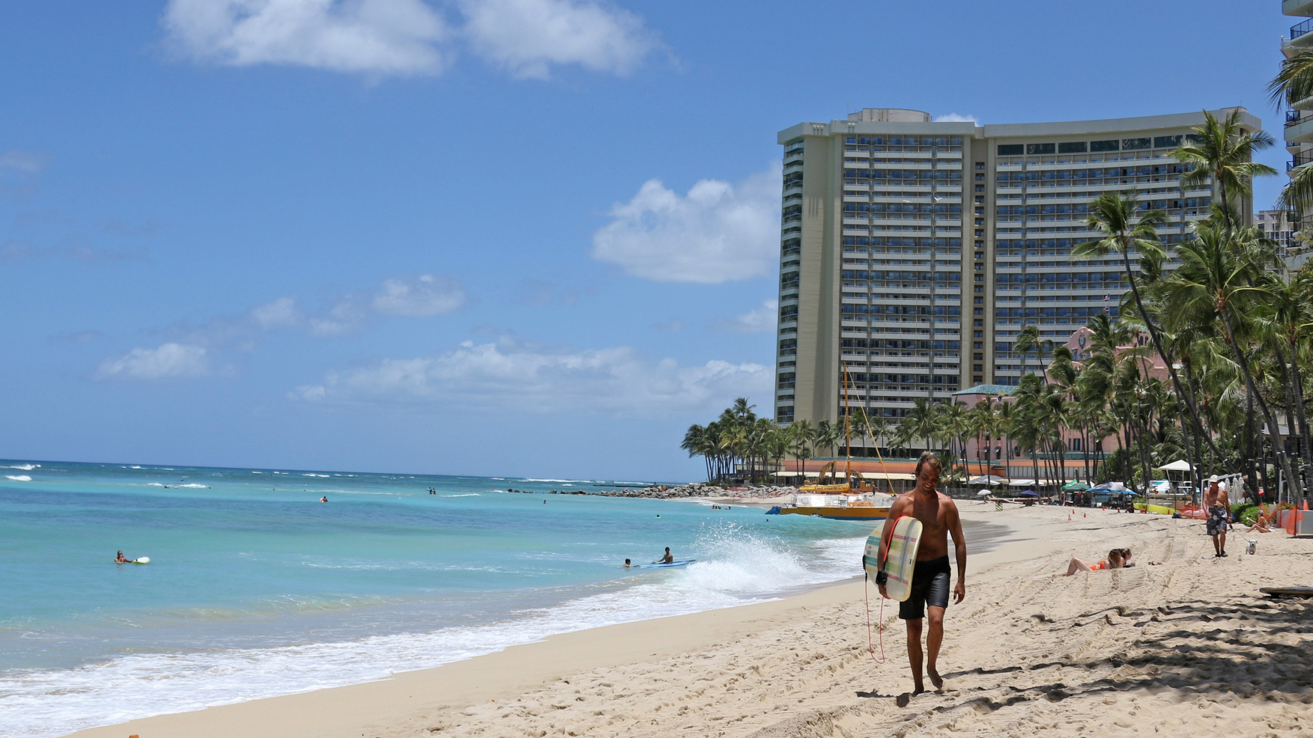 In this June 5, 2020, file photo, a surfer walks on a sparsely populated Waikiki Beach in Honolulu. Hawaii's governor says that starting Oct. 15, travelers arriving from out of state may bypass a 14-day quarantine requirement if they test negative for COVID-19. (AP Photo/Audrey McAvoy)