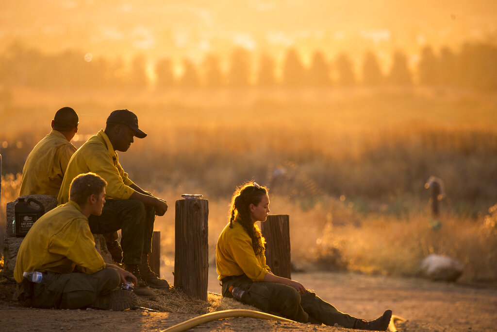 Firefighters rest during a wildfire in Yucaipa on Sept. 5, 2020. (AP Photo/Ringo H.W. Chiu)