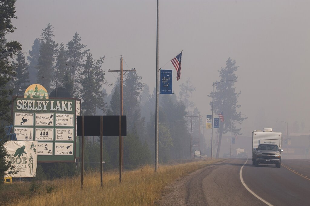 In this Aug. 10, 2017, file photo provided by the U.S. Forest Service, a pickup truck pulls a camper through the wildfire smoke in Seeley Lake in Missoula County, Montana. The small town was blanketed with hazardous smoke due to wildfires for seven weeks in 2017. (Kari Greer, U.S. Forest Service via AP, File)