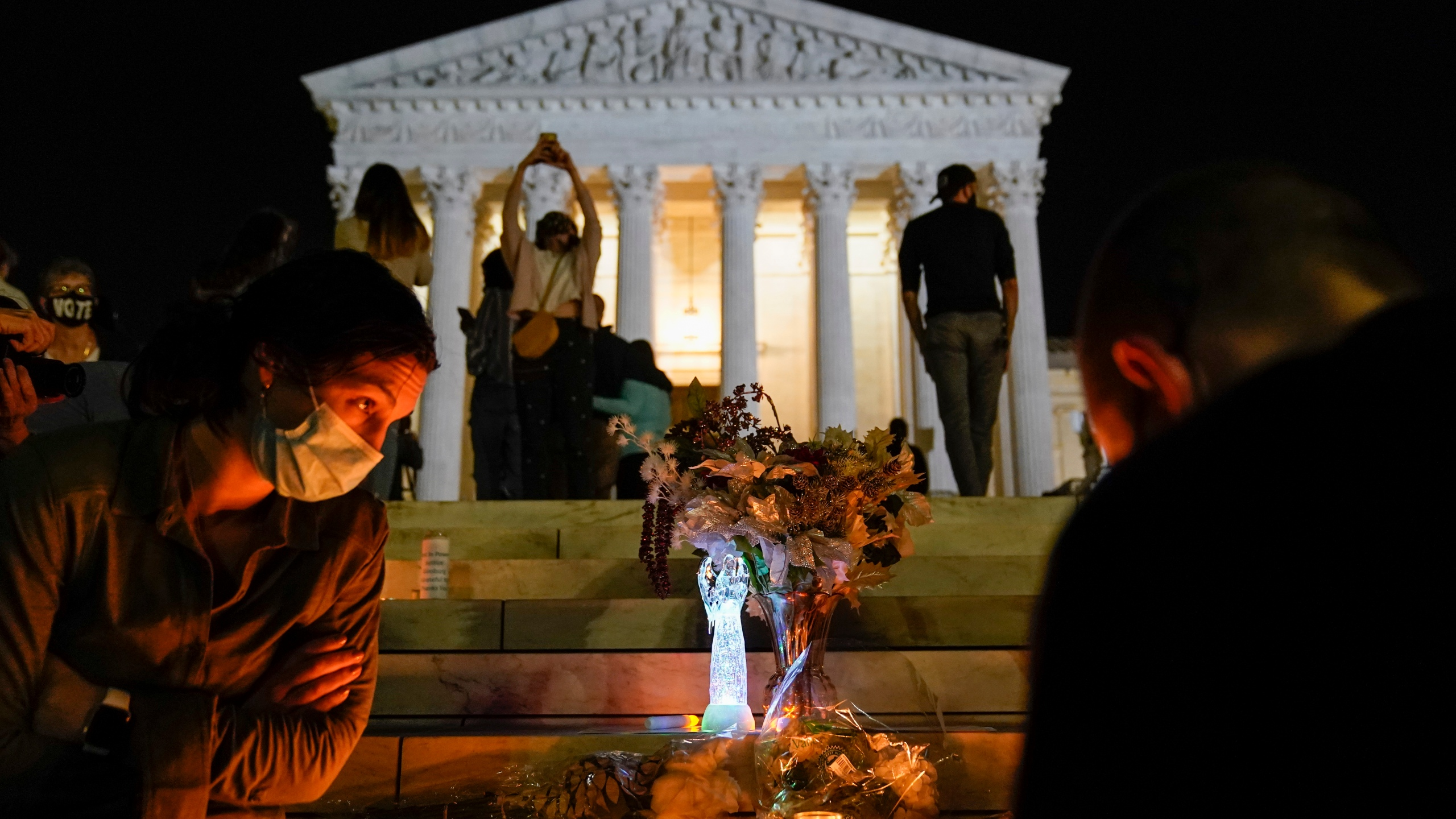People gather at the Supreme Court on Sept. 18, 2020, after the court announced that Justice Ruth Bader Ginsburg died of metastatic pancreatic cancer at age 87. (Alex Brandon / Associated Press)