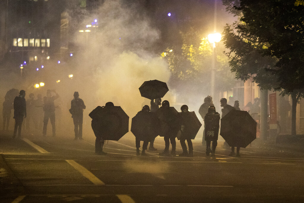 Tear gas fills the air during protests on Sept. 18, 2020, in Portland, Oregon. (AP Photo/Paula Bronstein)