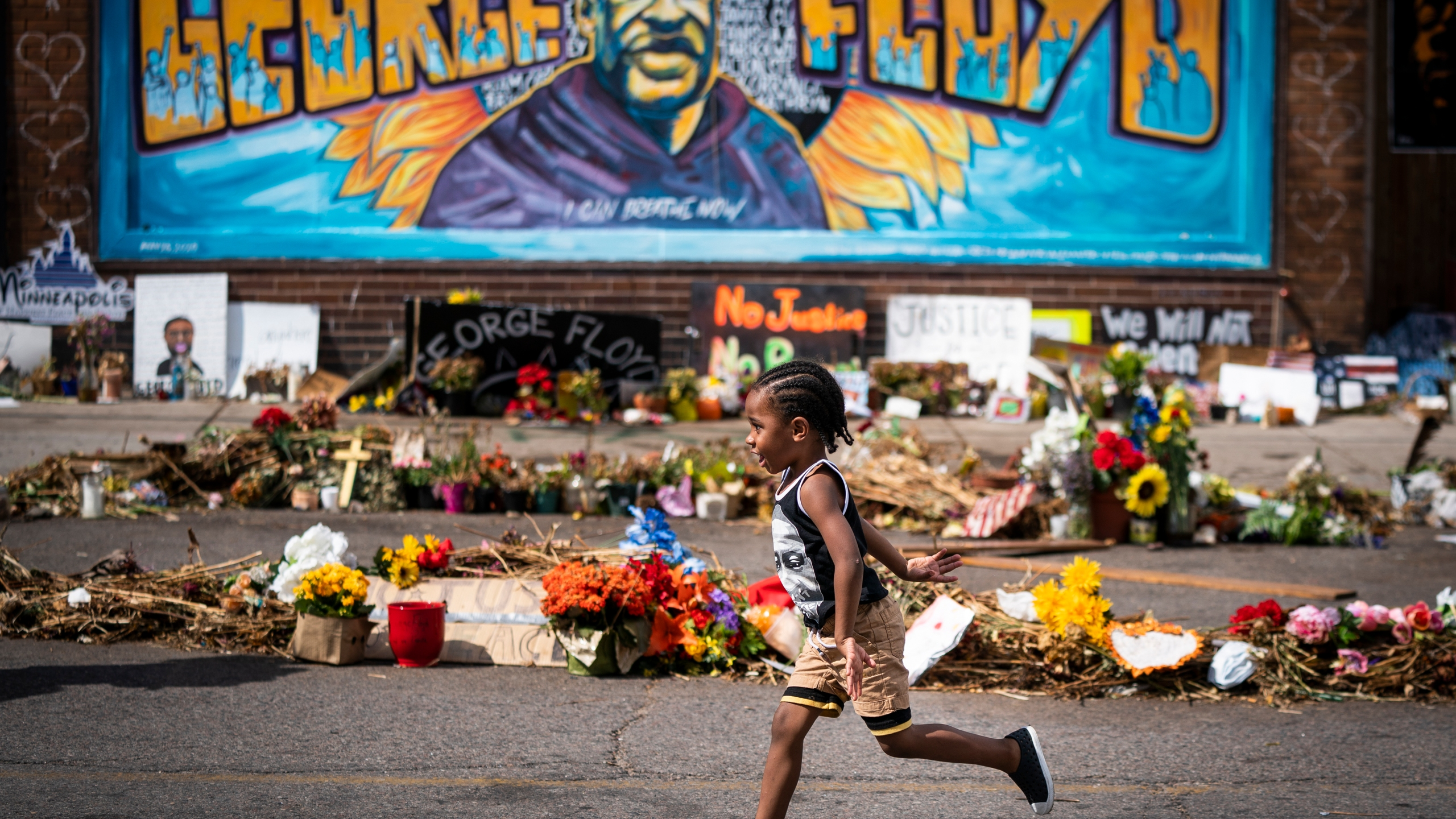 In this June 25, 2020 file photo, Carter Sims, 3, of Pine Island, Minn., runs past a mural at the George Floyd memorial outside Cup Foods in Minneapolis. (Leila Navidi/Star Tribune via AP, File)