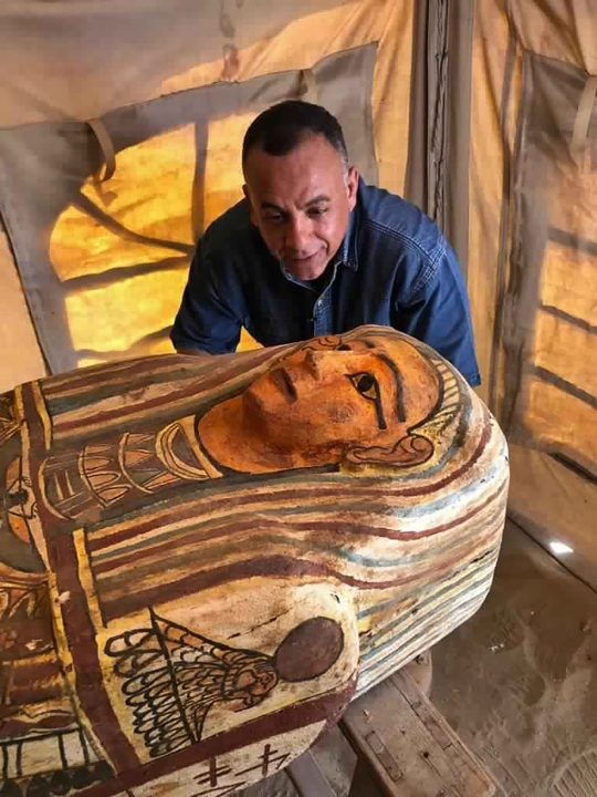 This September 2020 photo provided by the Ministry of Tourism and Antiquities shows Mostafa Waziri, secretary general of the Supreme Council of Antiquities, posing with one of more than two dozen ancient coffins unearthed near the famed Step Pyramid of Djoser in Saqqara, south of Cairo, Egypt. (Ministry of Tourism and Antiquities via AP)