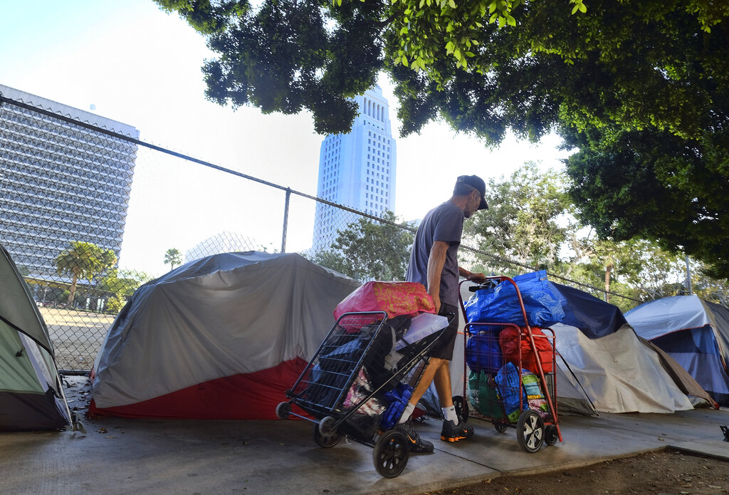 In this Monday, July 1, 2019, file photo, a homeless man moves his belongings from a street behind Los Angeles City Hall as crews prepared to clean the area. (AP Photo/Richard Vogel, File)
