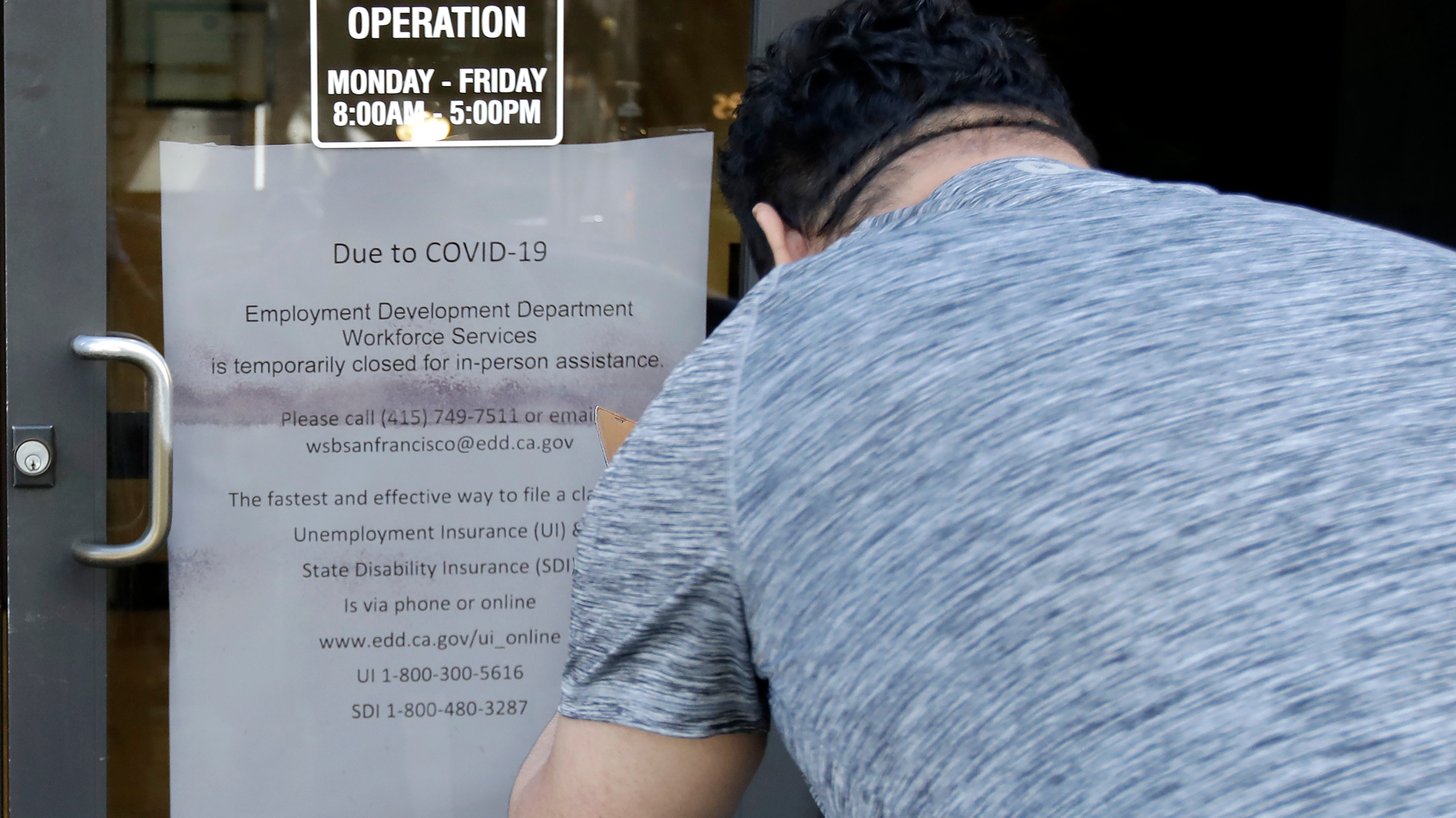 In this March 26, 2020 file photo, a man takes a photo of a sign advising that a Employment Development Department office in San Francisco is closed due to coronavirus concerns. (Jeff Chiu/Associated Press)