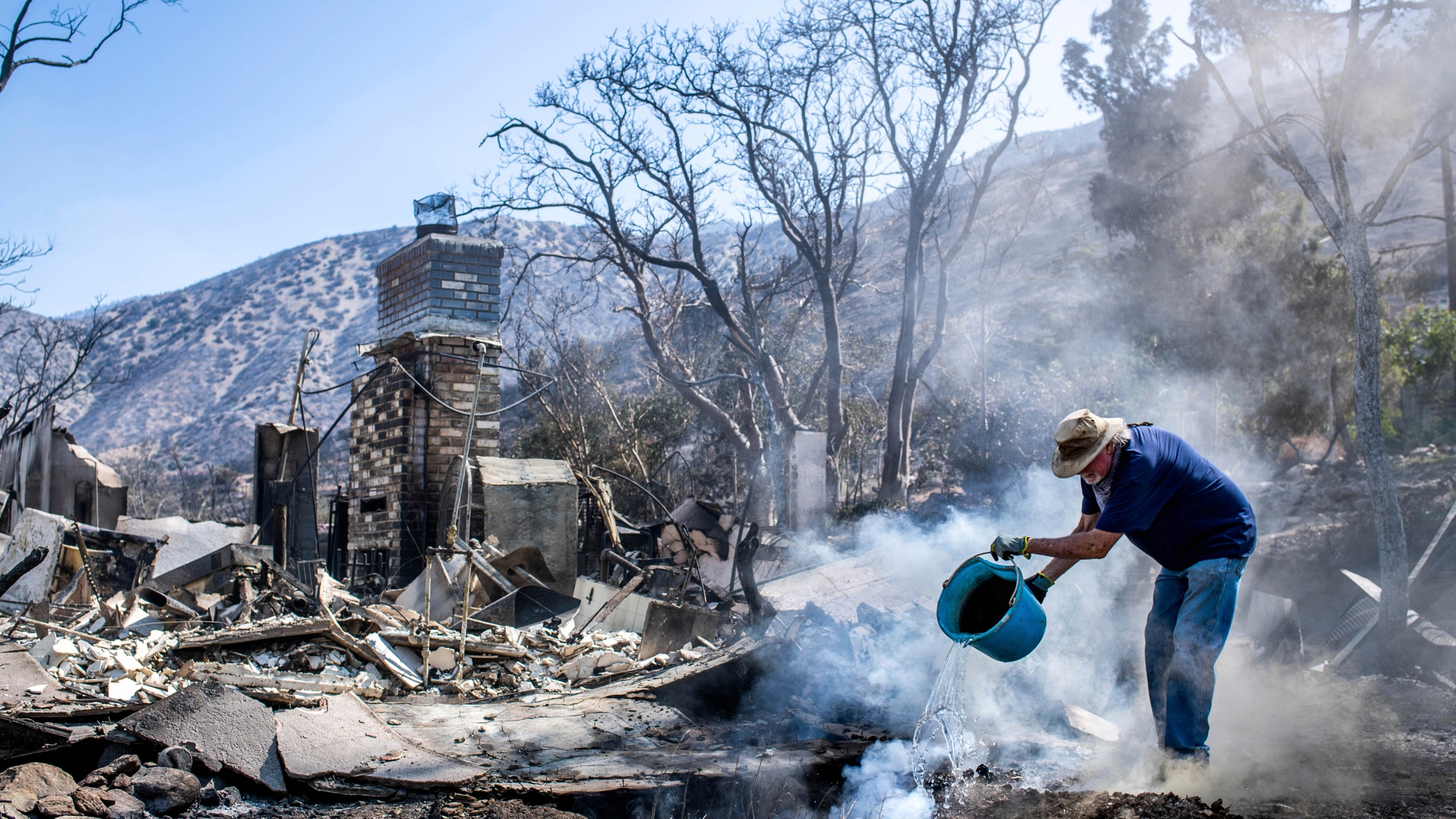 Dale Burton, of Leona Valley, tries to put out the fire that continues to smolder at his friend Cheryl Poindexter's property on Monday, Sept. 21, 2020, after the Bobcat Fire burned her home of 27 years and the 11-acre property where she ran an animal rescue in Juniper Hills. (Sarah Reingewirtz/The Orange County Register via AP)