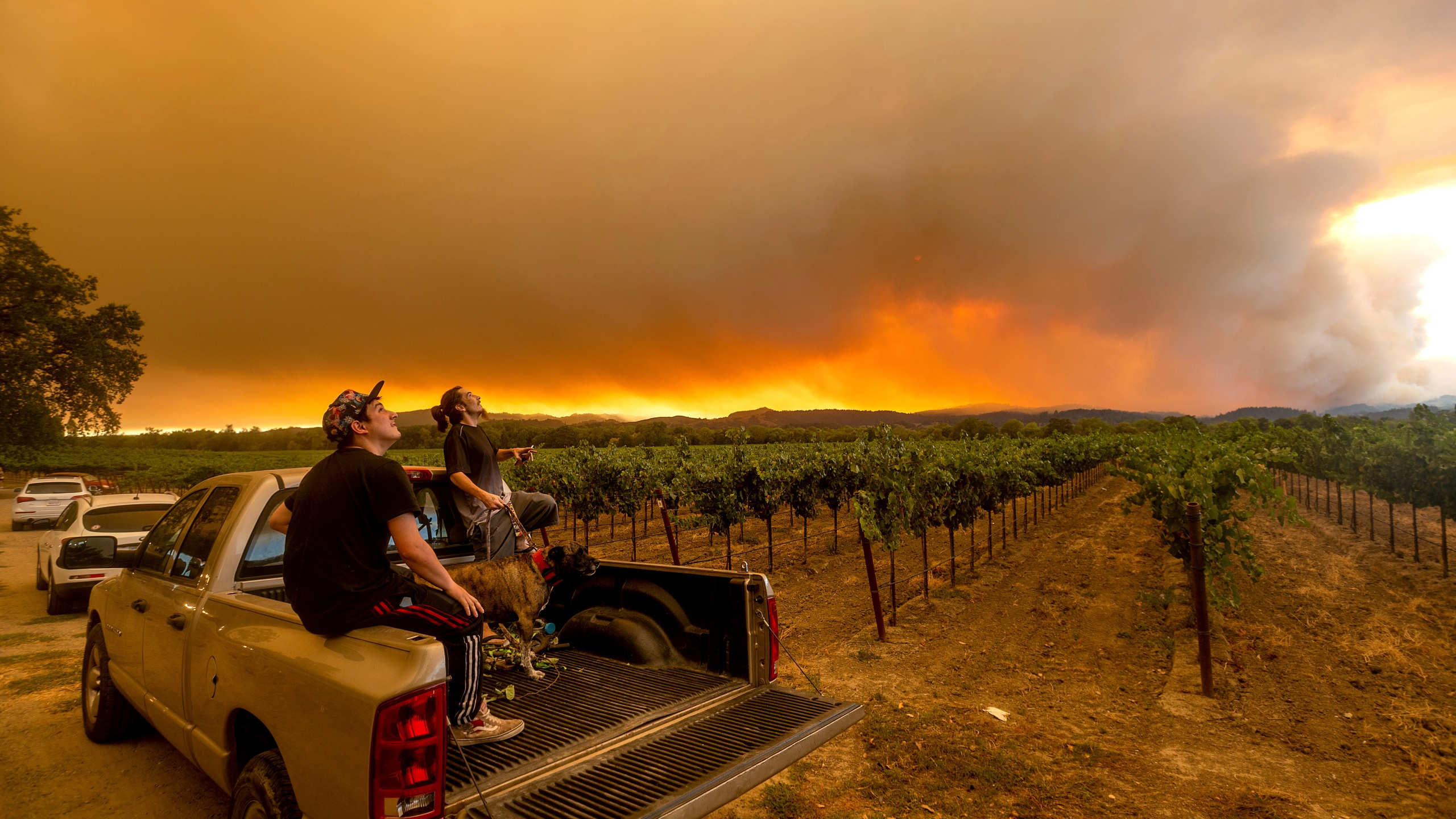 In this Aug. 20, 2020, photo, Thomas Henney, right, and Charles Chavira watch a plume spread over Healdsburg, Calif., as the LNU Lightning Complex fires burn. (AP Photo/Noah Berger, File)