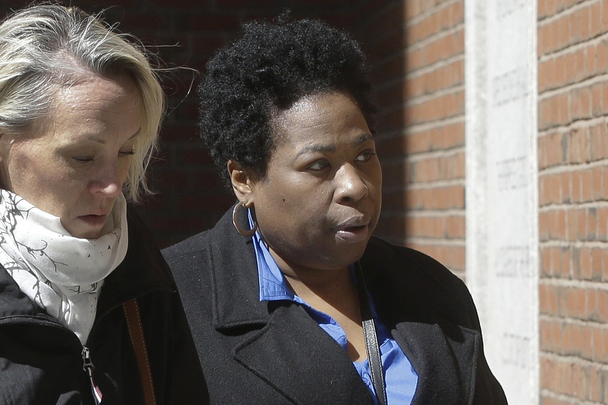 In this March 25, 2019, file photo, Niki Williams, right, a college entrance exam administrator, arrives at federal court in Boston to face charges in a nationwide college admissions bribery scandal. Williams pleaded guilty to charges on Friday, Sept. 25, 2020. (AP Photo/Steven Senne, File)