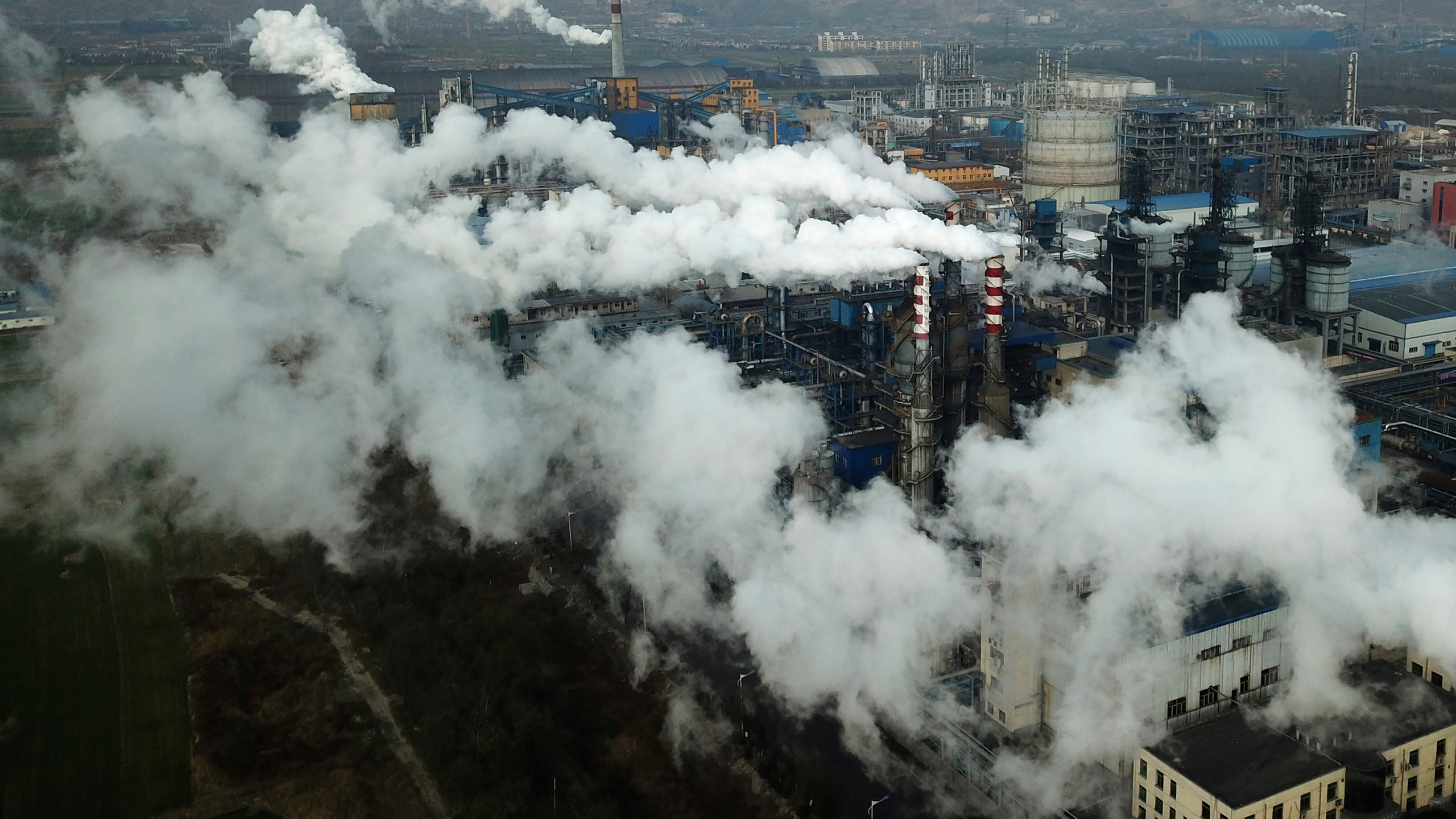 In this Nov. 28, 2019, photo, smoke and steam rise from a coal processing plant in Hejin in central China's Shanxi Province. (AP Photo/Sam McNeil, File)