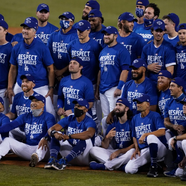 The Los Angeles Dodgers pose for a photo after the Dodgers clinched the NL West title with a 7-2 win over the Oakland Athletics in a baseball game on Sept. 22, 2020, in Los Angeles. (AP Photo/Ashley Landis)