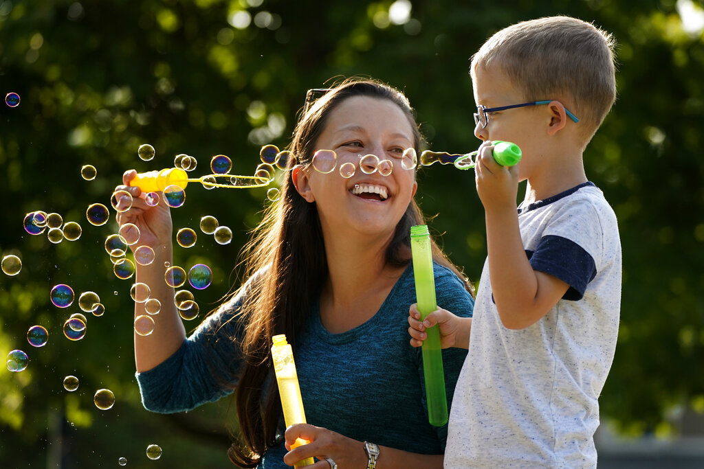 Claire Reagan plays with her son Evan, 5, Monday, Sept. 21, 2020, outside her home in Olathe, Kansas. (AP Photo/Charlie Riedel)
