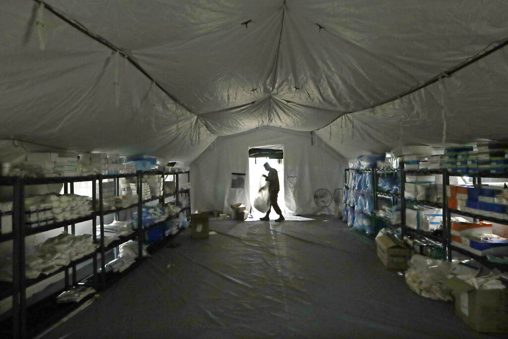 In this March 31, 2020, file photo a U.S. Army soldier walks inside a mobile surgical unit being set up by soldiers from Fort Carson, Col., and Joint Base Lewis-McChord (JBLM) as part of a field hospital inside CenturyLink Field Event Center, in Seattle. (AP Photo/Elaine Thompson, File)